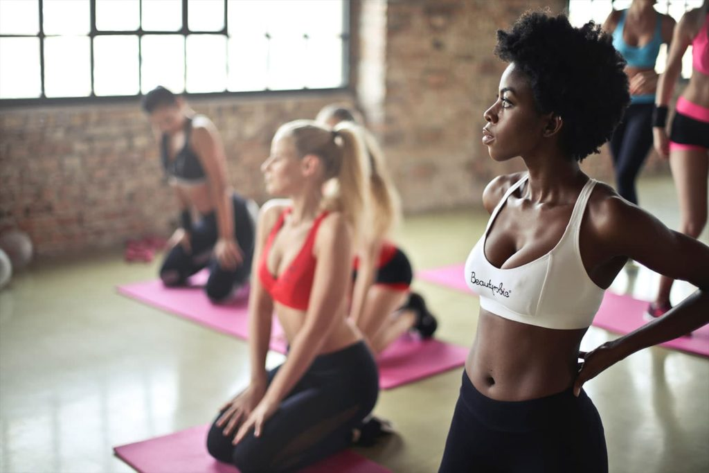 two woman standing at yoga class