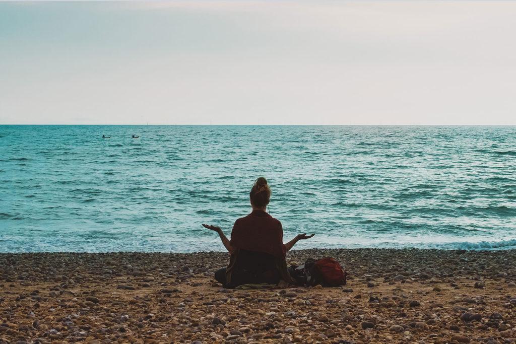 a woman meditating ocean side
