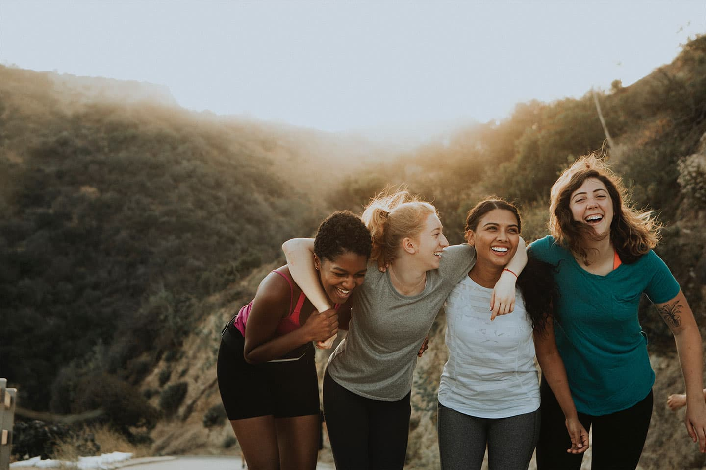 group of woman smiling together after a hike