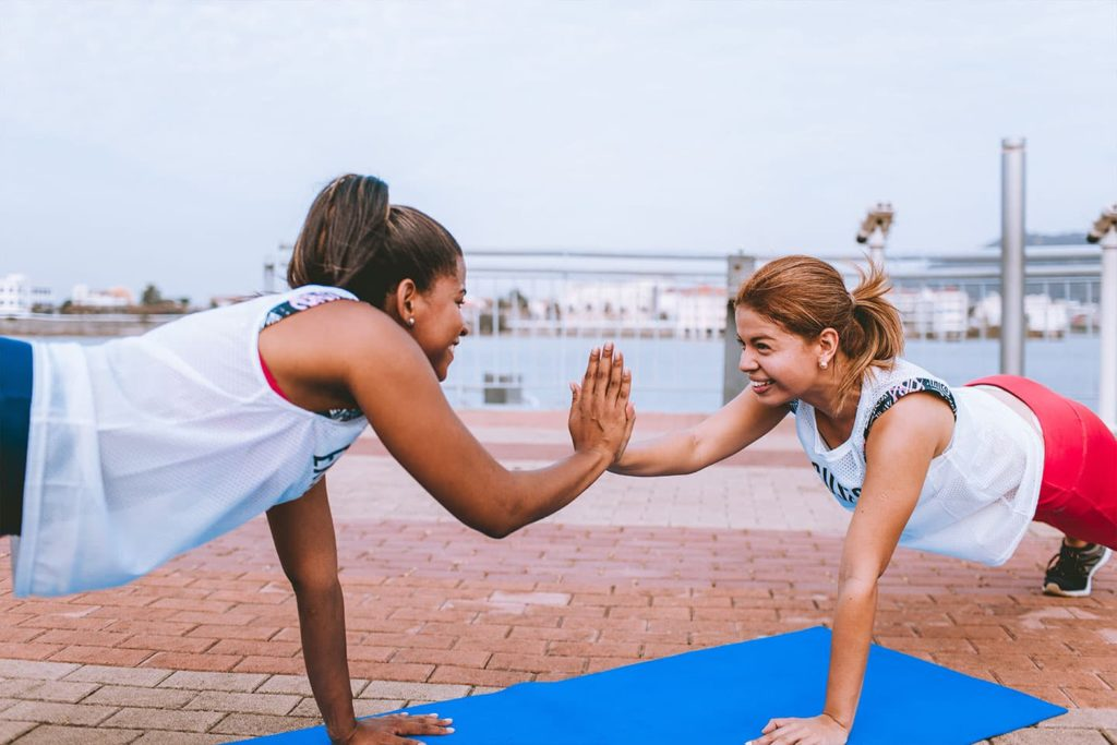 two women locking hands during workout