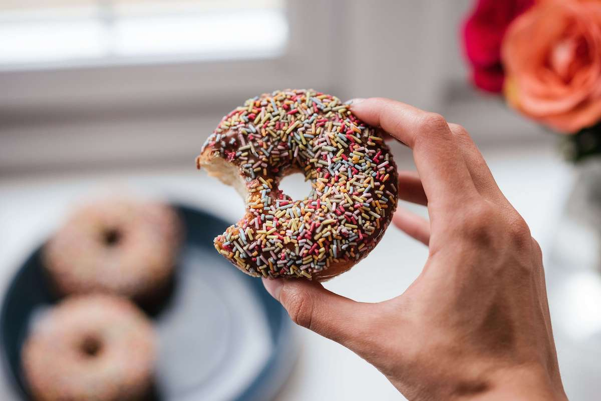 hand holding a chocolate sprinkled donut
