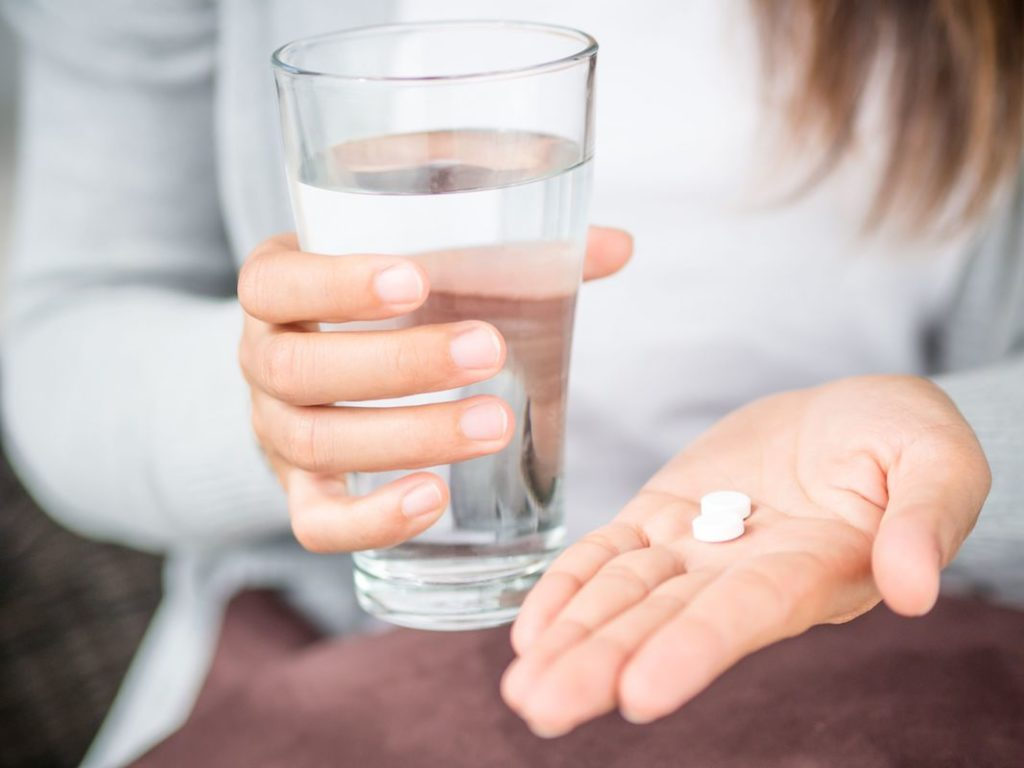 woman holding white pill tablets in hand with glass of water