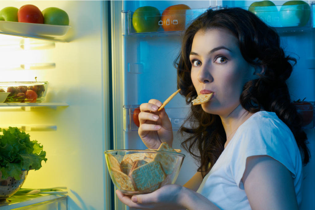 Woman by her fridge eating a late night snack of crackers