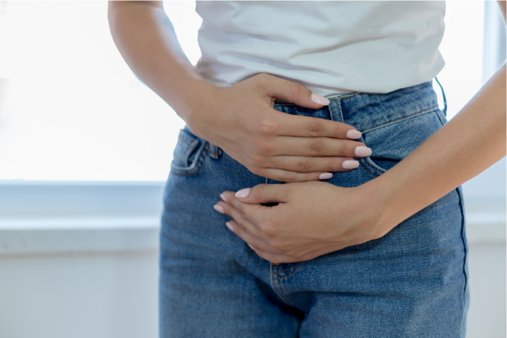 Woman in white shirt and jeans holding her upset stomach