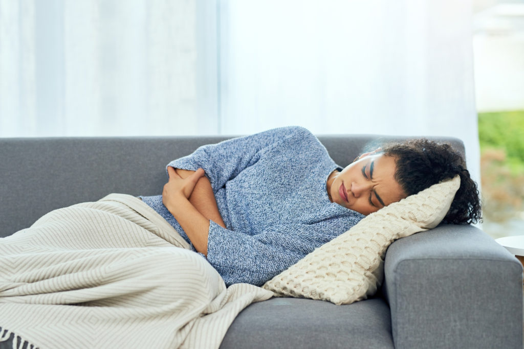 woman laying on couch holding stomach in pain from fibromyalgia and IBS