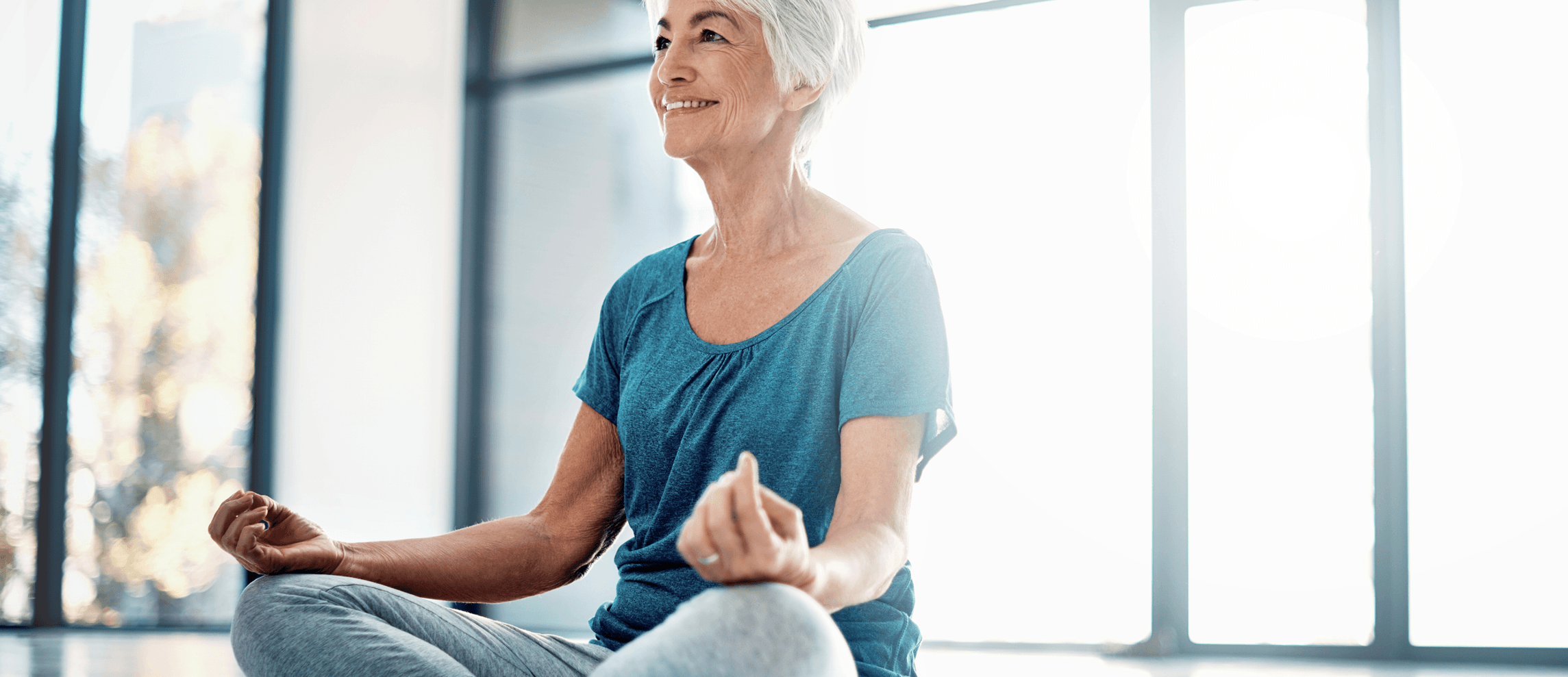 older woman smiling and sitting in yoga pose