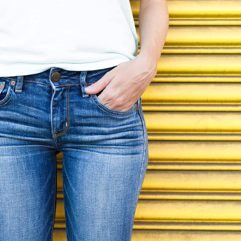 Woman in jeans standing on front of yellow gate