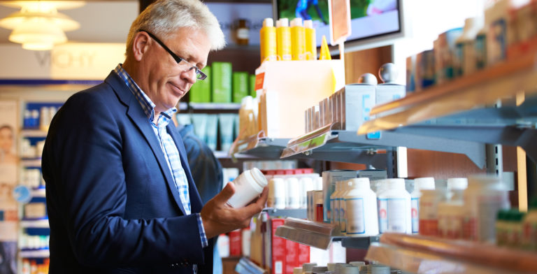 Older man selecting medication from a store shelf.