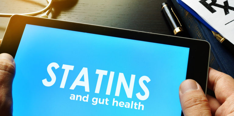 "person holding tablet that displays text: ""Statins and gut health"""