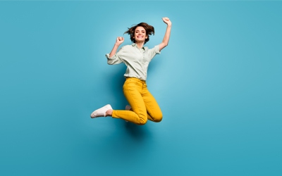 Woman in green shirt and yellow pants jumping for joy