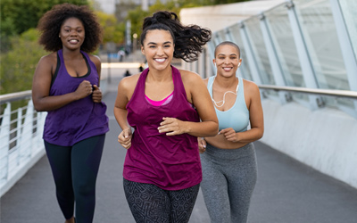 Three woman smiling on a run outside