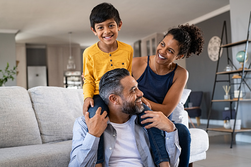 family of three smiling in front of couch. Son on shoulders of father and mother to their side.