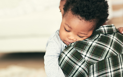 african american baby sleeping on the shoulder of parent