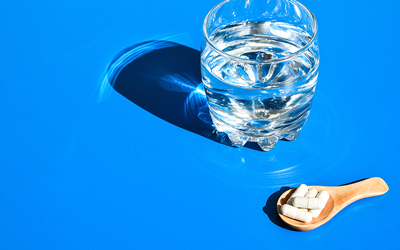 Glass of water next to five capsules. Text: 4 Good Reasons Why You Need A Probiotic