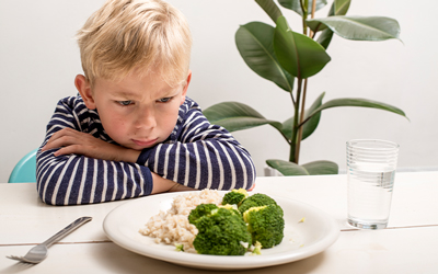 Young boy in striped shirt frowning at kitchen table with arms folded staring at a plate with broccoli and rice.
