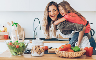 Mother and young daughter having fun in the kitchen. Daughter on mother's back. Salad, vegetables, and cookie jar on the table in foreground.