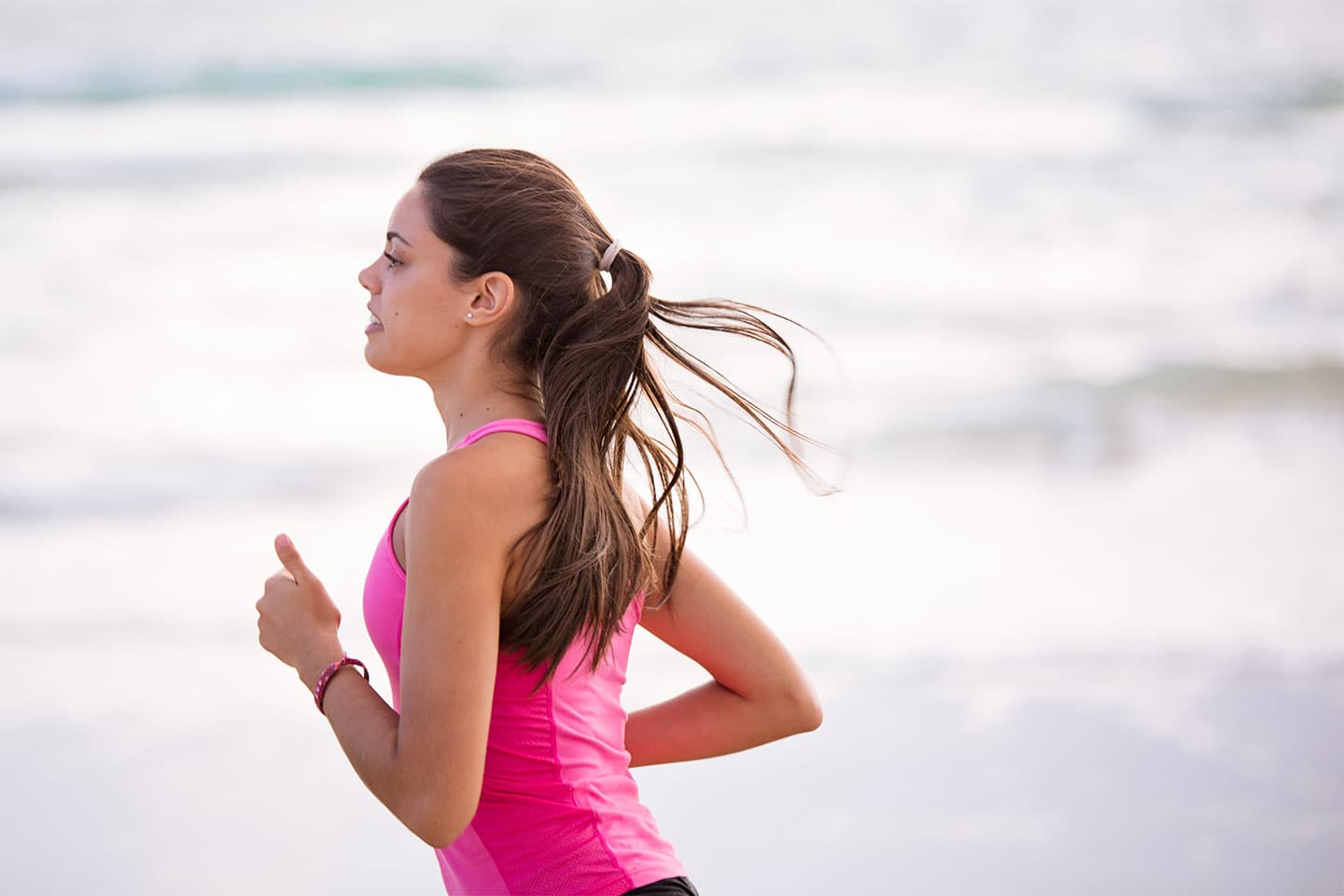 Woman with pony tail in pink tank top running on beach shore