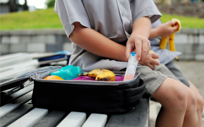 Child prepared for food allergy reaction with epipen in lunchbox
