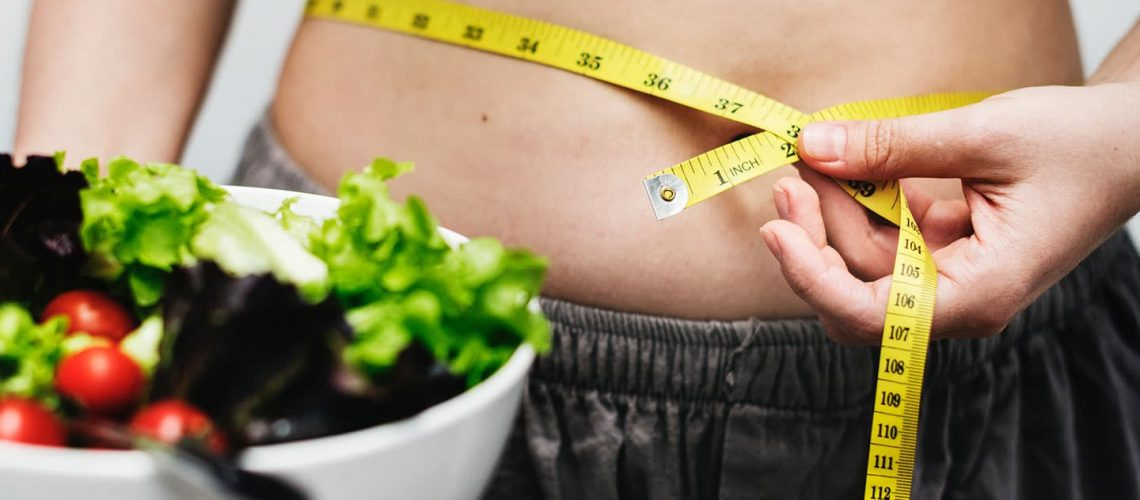 a woman holding a salad and measuring her waist