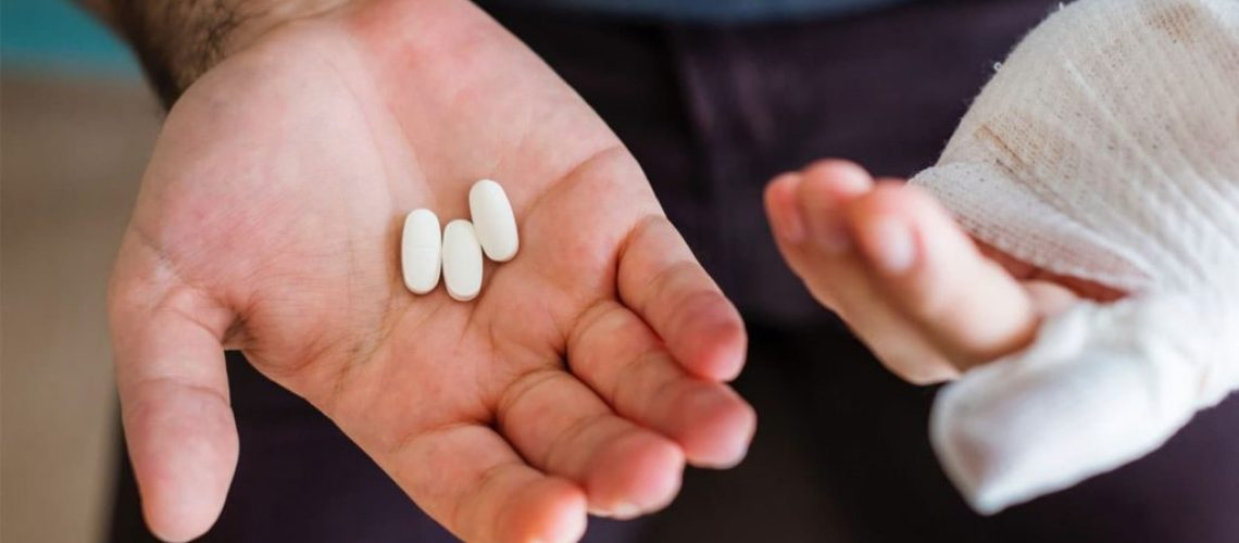 person holding painkiller